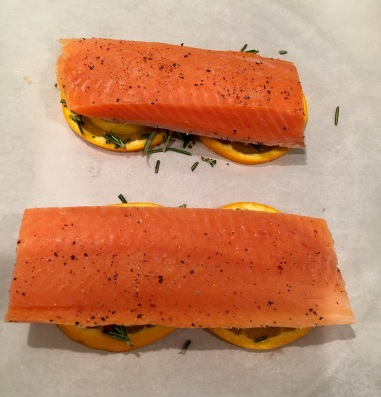 The seasoned salmon is placed atop the bottom layer of prepared citrus slices